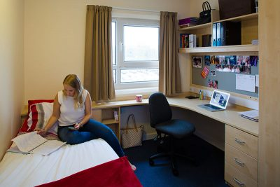 a woman sitting on a bed in a student bedroom